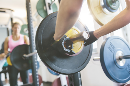 motivations: Close-up of womans hand putting weights on a barbell in gym