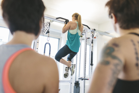 Two women watching athlete doing pull-ups in gym LANG_EVOIMAGES