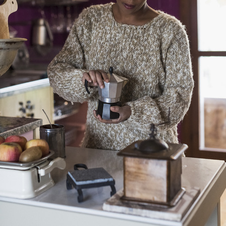 Young woman in kitchen preparing coffee LANG_EVOIMAGES