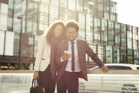 lighted: Two smiling young business people outdoors looking at smartphone