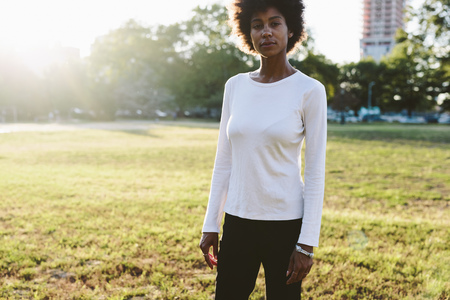 sweatshirt: Young woman standing on a meadow of a park at backlight
