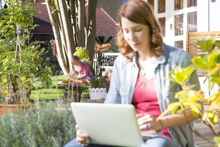 three generations: Young woman using laptop in garden with mother and daughter in background