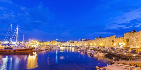 Greece, Rhodes, harbor, city wall and fishing boats at dusk LANG_EVOIMAGES