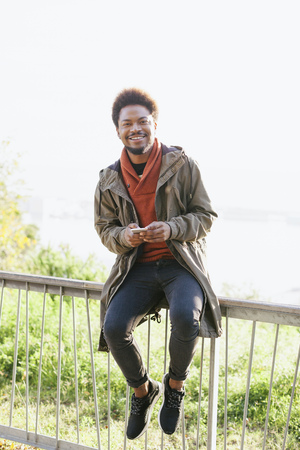 Portrait of smiling young man with smartphone sitting on a railing