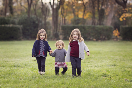 France, Provence, Marseille, Parc de Maison Blanche, three toddler girls holding hands in a field LANG_EVOIMAGES