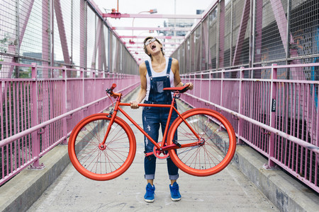 USA, New York City, Williamsburg, woman with red racing cycle on Williamsburg Bridge LANG_EVOIMAGES