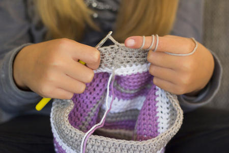 Girl crocheting a cap, close-up