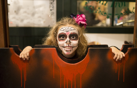 morbidity: Blond little girl with sugar skull makeup at Halloween LANG_EVOIMAGES