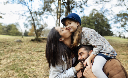Parents and daughter having fun together in nature