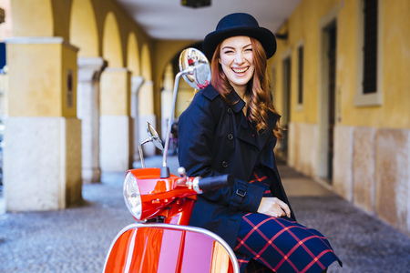 Italy, Verona, happy young woman with scooter LANG_EVOIMAGES