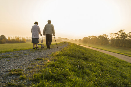 dikes: Senior couple walking with walking stick and wheeled walker in the nature