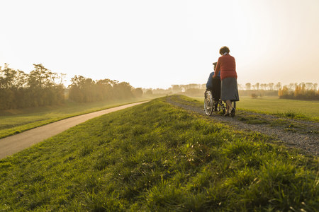 lighted: Senior woman pushing husband in wheelchair in the nature LANG_EVOIMAGES