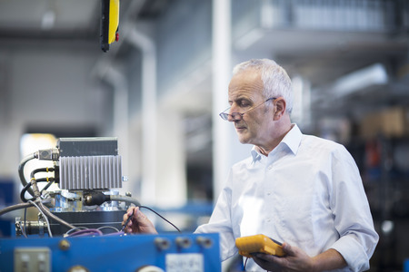 Man controlling device with voltmeter in an industrial hall LANG_EVOIMAGES