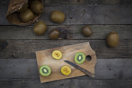 interiour shots: Green and golden kiwis on chopping board, wood
