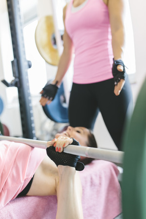 motivations: Two women doing barbell bench presses in a power rack LANG_EVOIMAGES