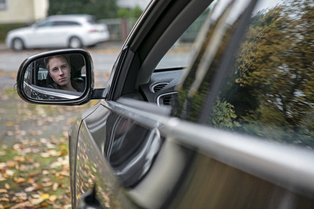 drive through: Reflection of young man in wing mirror LANG_EVOIMAGES