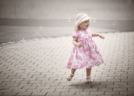 Happy blond little girl wearing hat and summer dress with floral design  dancing on pavement