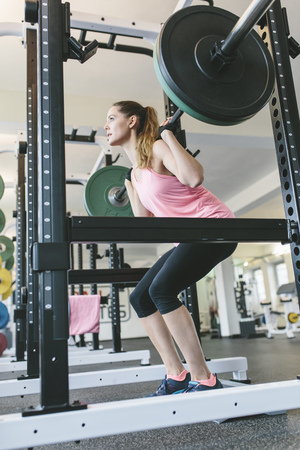 Woman doing barbell squats in a power rack LANG_EVOIMAGES