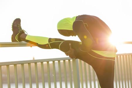 motivations: Athlete stretching on bridge railing