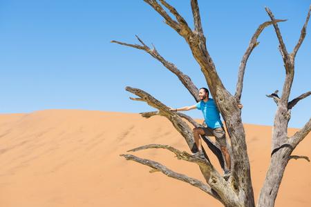 clime: Namibia, Namib Desert, man on dead tree in Deadvlei LANG_EVOIMAGES