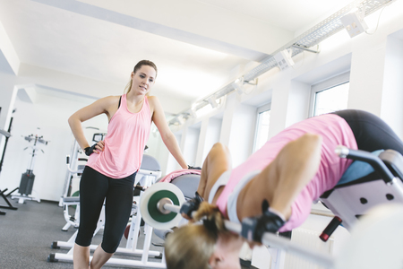 Woman doing weighted back extensions in gym LANG_EVOIMAGES