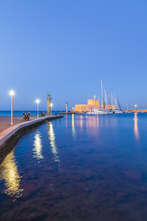 Greece, Rhodes, entrance to Mandraki harbour at blue hour