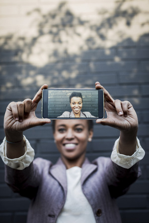 hands free phone: Photography of young woman taking a selfie on display of smartphone