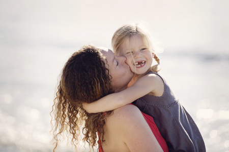 Mother kissing her little daughter with toothgap in front of the sea