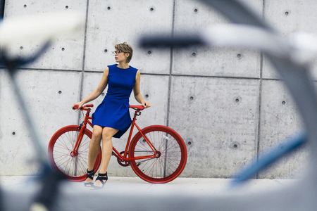 Woman with red racing cycle in front of concrete wall LANG_EVOIMAGES