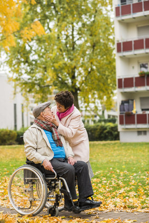 Senior woman looking at husband in wheelchair