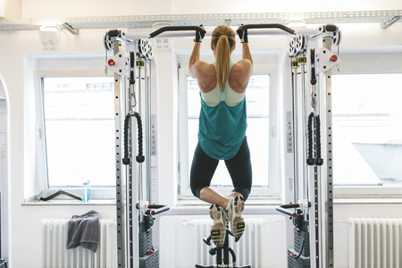 motivations: Woman doing pull-ups in gym