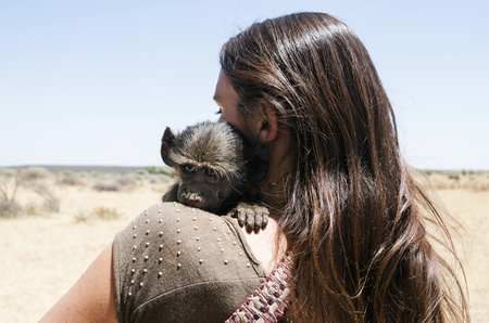 Namibia, back view of woman holding baby baboon