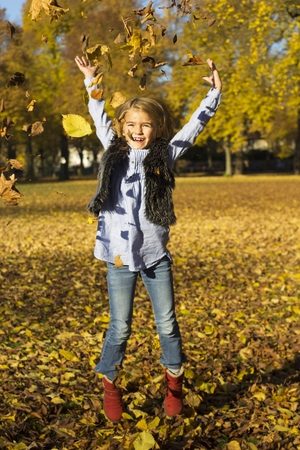 Happy little girl throwing autumn leaves while jumping in the air LANG_EVOIMAGES