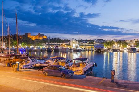 lighted: Greece, Rhodes, boats at Mandraki harbour at dusk LANG_EVOIMAGES