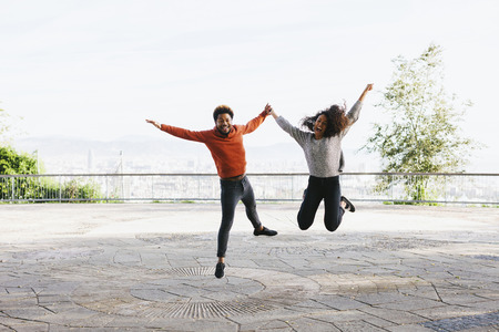 Spain, Barcelona, portrait of happy young couple jumping in the air on view terrace LANG_EVOIMAGES