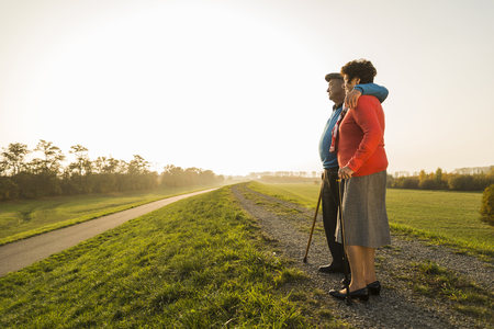 dikes: Senior couple with walking sticks standing in the nature LANG_EVOIMAGES