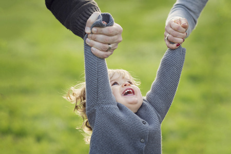ardor: Toddler girl holding by the hands of her parents