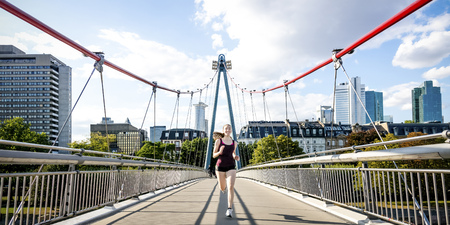 Germany, Frankfurt, young woman jogging on bridge LANG_EVOIMAGES