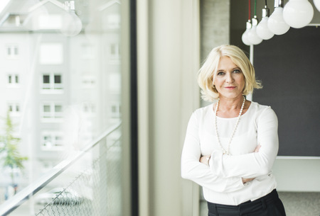 motivations: Portrait of smiling blond businesswoman with crossed arms