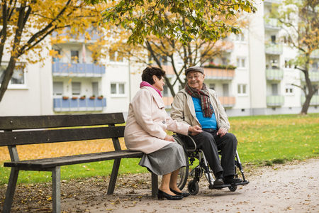 Senior woman sitting on bench next to husband in wheelchair