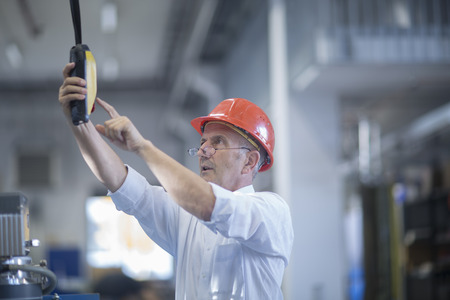 Man with red safety helmet operating lifting system
