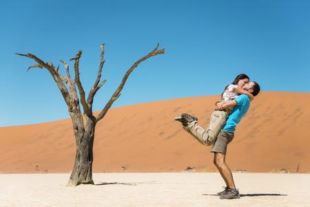 africa kiss: Namibia, Namib Desert, happy couple kissing next to dead tree in Deadvlei