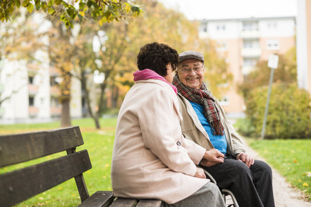 Senior man in wheelchair holding hands with wife on bench