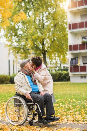 Senior woman kissing husband in wheelchair LANG_EVOIMAGES