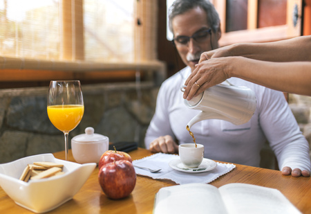 Man sitting at breakfast while woman pouring coffee into his cup