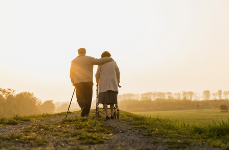 lighted: Senior couple walking with walking stick and wheeled walker in the nature