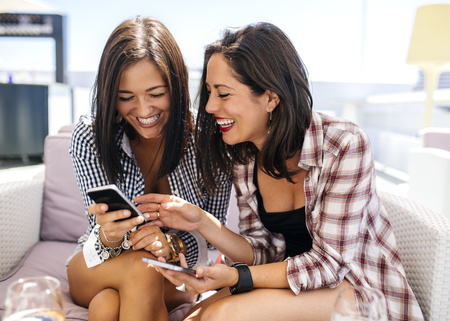 Two happy female friends on terrace looking at cell phone