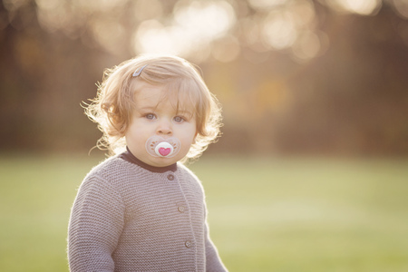 Portrait of baby girl with pacifier at backlight LANG_EVOIMAGES