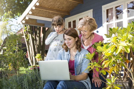 three generations: Grandmother, mother and daughter looking at laptop on garden terrace LANG_EVOIMAGES