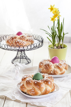 Braided Easter bread with coloured eggs and daffodil LANG_EVOIMAGES